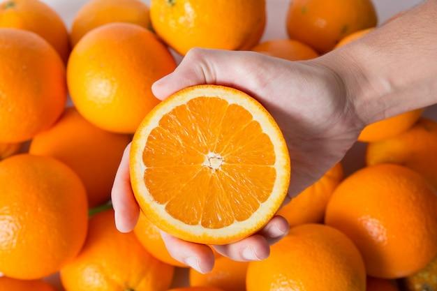Persoon die gesneden oranje helft over stapel van vruchten toont