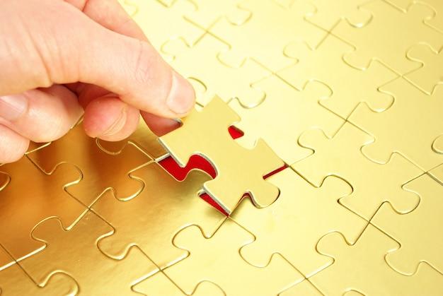 Persoon die gouden puzzel beëindigt
