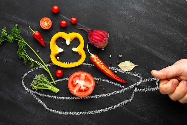 Persoon die groenten op krijtpan koken