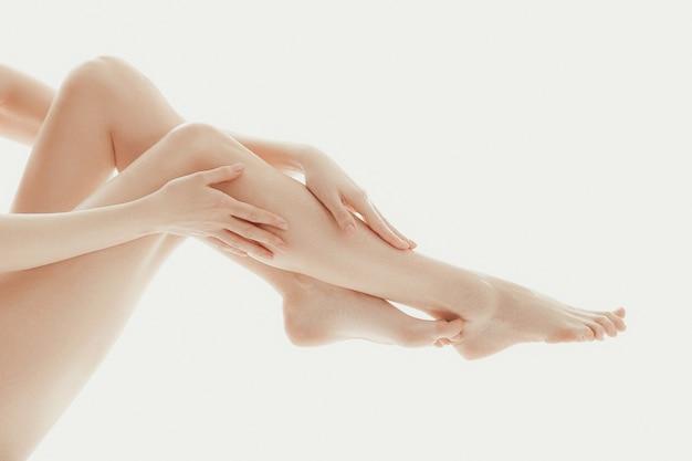 Persoon die haar benen aanraakt met haar vingers