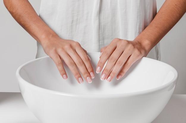 Persoon die haar handen boven de gootsteen droogt