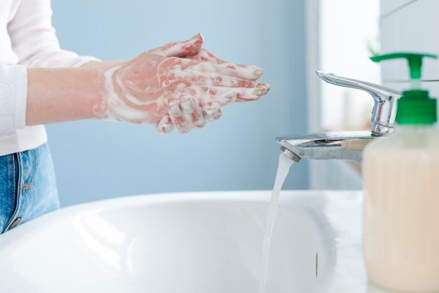 Persoon die haar handen wast met water en zeep