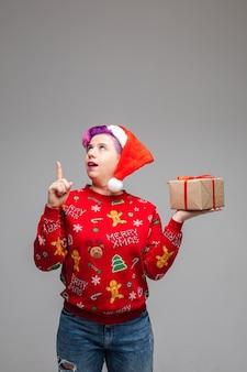 Persoon die haar vinger met een geschokte gezichtsuitdrukking naar het plafond opheft terwijl ze een ingepakte doos in de hand heeft. nieuwjaar concept