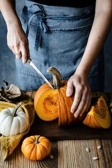 Persoon die halloween-pompoen snijdt