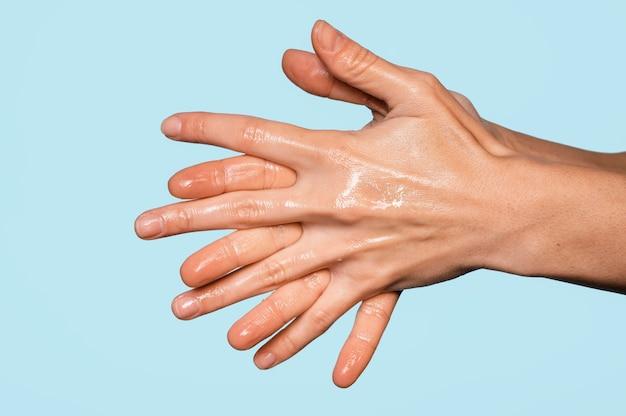 Persoon die handen binnenshuis wast
