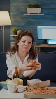 Persoon die heerlijke hamburger en friet eet in de woonkamer