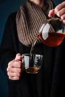 Persoon die heerlijke thee in een kop giet