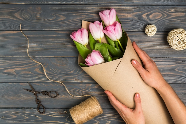 Persoon die heldere tulpen in pakpapier verpakken
