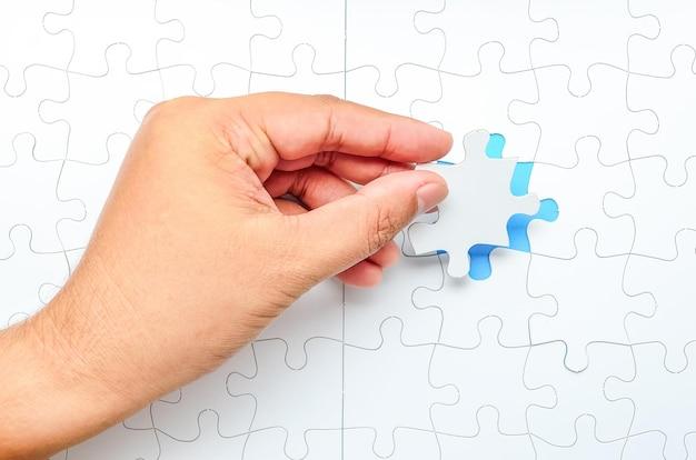Persoon die het laatste puzzelstukje past. concept afbeelding van gebouw en knop omhoog