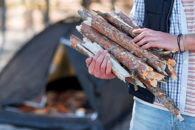 Persoon die hout verzamelt voor kampvuur