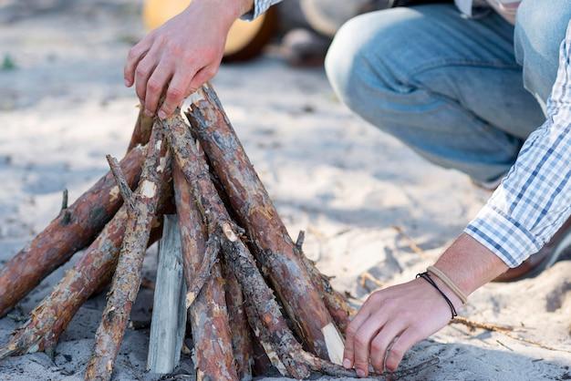 Persoon die hout voor kampvuur regelt