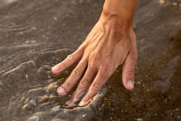 Persoon die hun hand in het water bij het strand