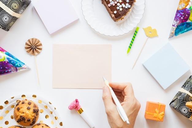 Persoon die iets op een lege verjaardagskaart wil schrijven