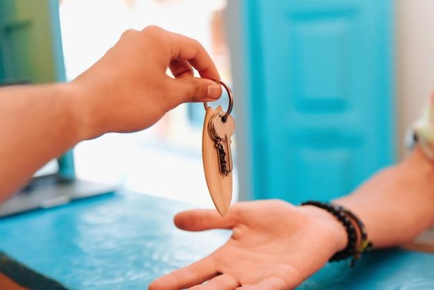 Persoon die in een hotel verblijft, geeft bij het inchecken de sleutels aan de receptioniste