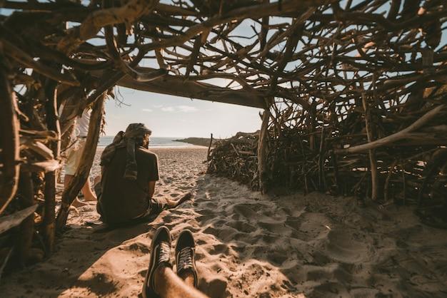 Persoon die in een houten grot zit en een foto neemt van een persoon die op het zand bij de zee zit