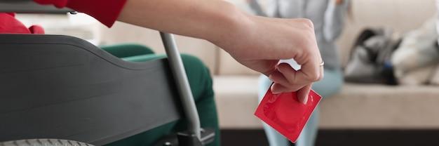 Persoon die in een rolstoel zit, houdt een rood condoom in zijn hand voor een zittende vrouw