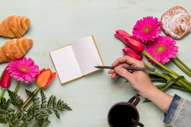 Persoon die in klein notitieboekje schrijft