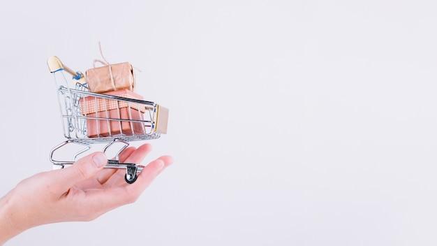 Persoon die kleine supermarktkar met giftdozen houdt
