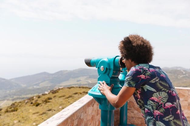 Persoon die landschap met verrekijkers bekijkt