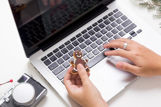 Persoon die laptop en eatign koekje gebruikt