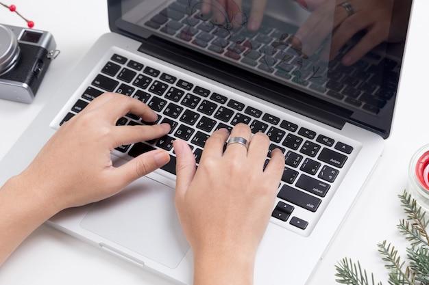 Persoon die laptop met kerstmisdecoratie op de lijst met behulp van