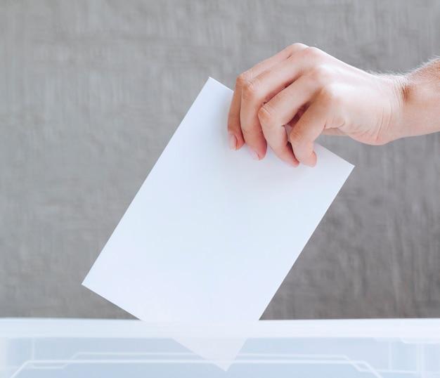 Persoon die lege stemming in een doos zet