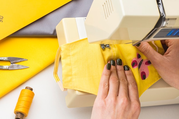 Persoon die machine gebruikt om gezichtsmaskers te naaien
