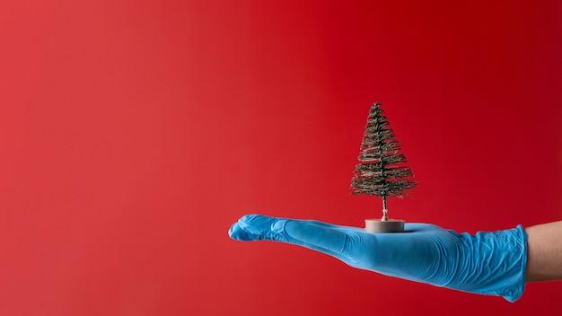 Persoon die medische handschoenen draagt die een boomstuk speelgoed houden
