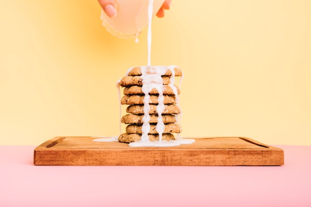 Persoon die melk van glas op koekjesstapel aan boord giet