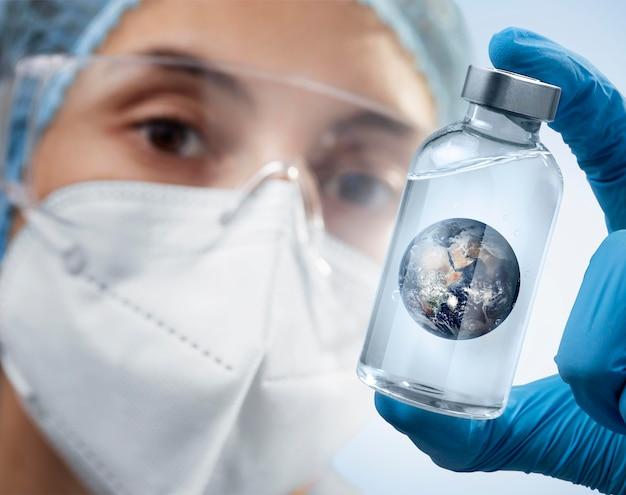 Persoon die met chirurgische handschoenen de aarde in een fles houdt