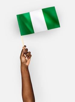 Persoon die met de vlag van de federale republiek nigeria zwaait