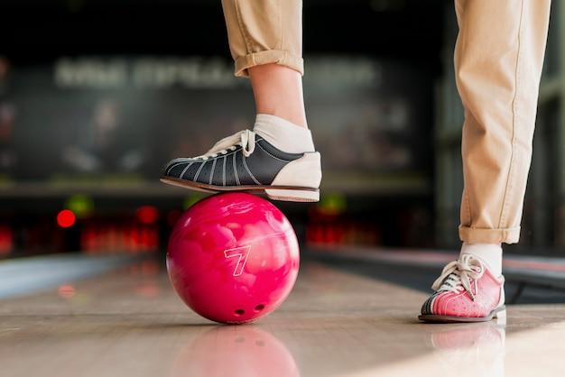 Persoon die met de voet een rode bowlingbal houdt