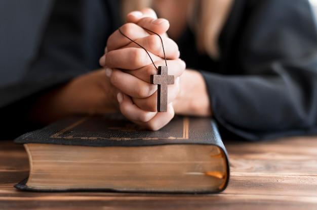 Persoon die met kruis en heilig boek bidt