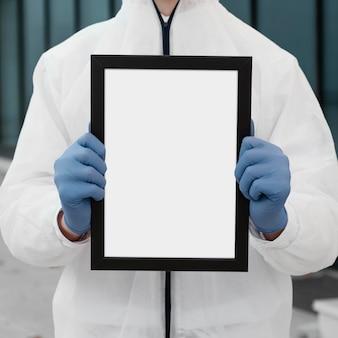 Persoon die met medisch masker een lege tablet houdt
