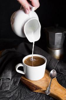 Persoon die mil in kop van koffie giet