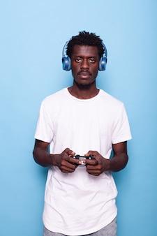 Persoon die naar de camera kijkt terwijl hij de controller en koptelefoon gebruikt