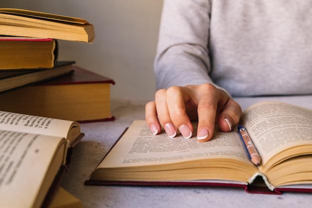 Persoon die naast boekstapel bestudeert