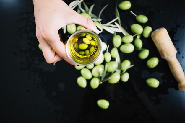 Persoon die olijfolie over olijven