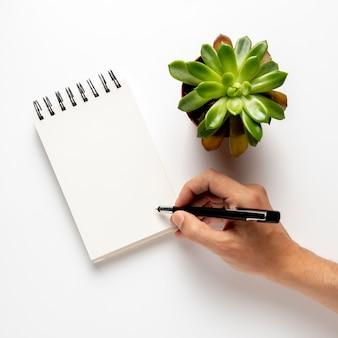 Persoon die op blocnote met pen schrijft