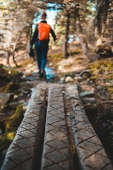Persoon die op bruine houten brug loopt