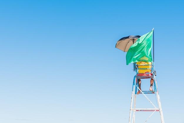 Persoon die op de veiligheidsstoel op het strand staat met een wuivende groene vlag