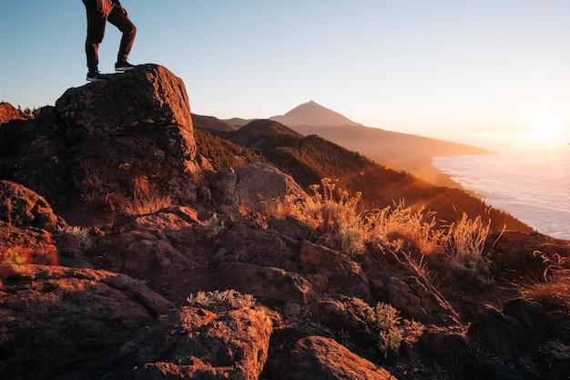 Persoon die op een rots staat omringd door de zee tijdens een heldere zonsondergang - concept van succes