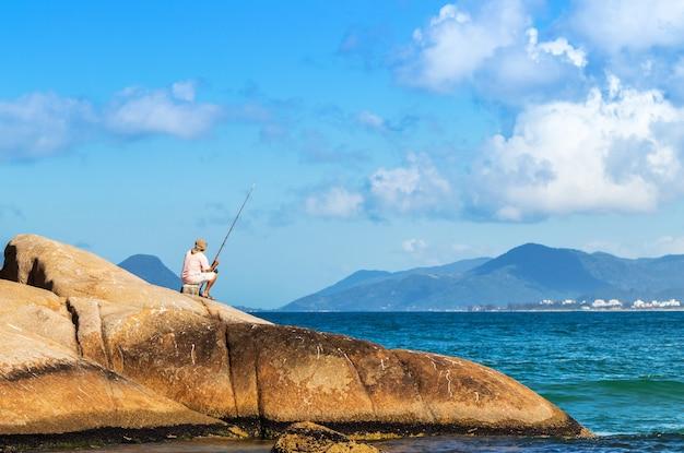 Persoon die op een rots zit te vissen op het joaquina-strand in florianopolis, brazilië