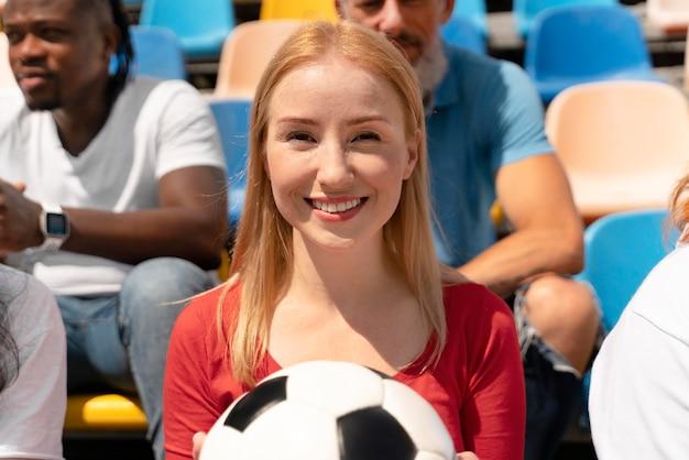 Persoon die op een zonnige dag naar een voetbalwedstrijd kijkt Gratis Foto