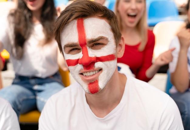 Persoon die op een zonnige dag naar een voetbalwedstrijd kijkt