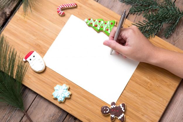 Persoon die op kerstkaart schrijft met eigengemaakte koekjes
