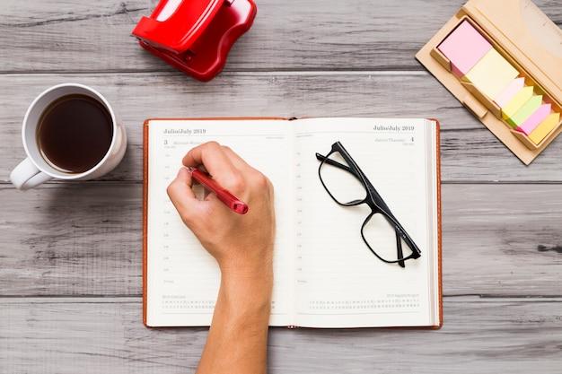 Persoon die op notitieboekje bij lijst schrijft