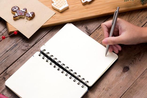 Persoon die op open notitieboekje met smakelijke kerstmis eigengemaakte koekjes schrijft