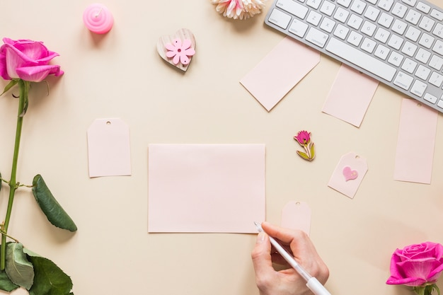 Persoon die op papier bij lijst met rozen schrijft
