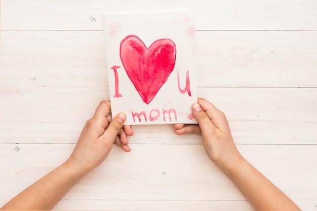 Persoon die papier met ik hou van je moeder inscriptie